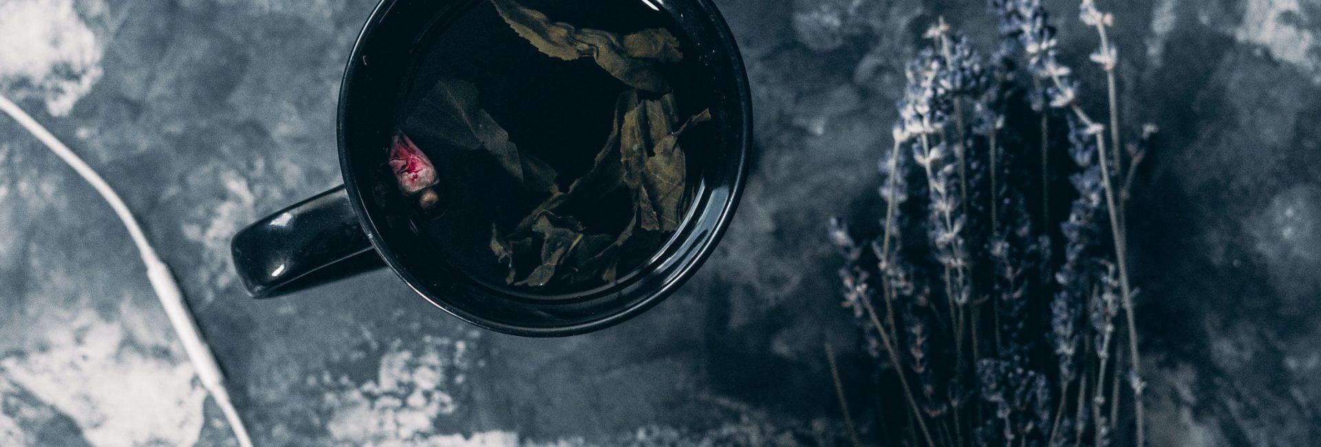 tea-in-black-ceramic-mug-near-apple-earpods-baja